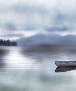 Barca in mezzo a un lago tranquillo e nebbioso
