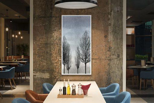 Silhouette di alberi spogli su sfondo grigio
