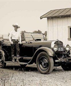 Vecchia foto con un cowboy e una vecchia automobile